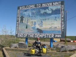 Mike on Bike in front of Welcome to Inuvik sign on the Dempster Highway in Canada's Northwest Territories.